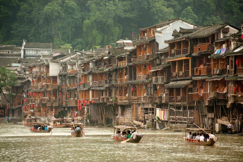 De toeristen ontspannen, nemen een rondvaart op de rivier in Fenghuang ancie stock foto
