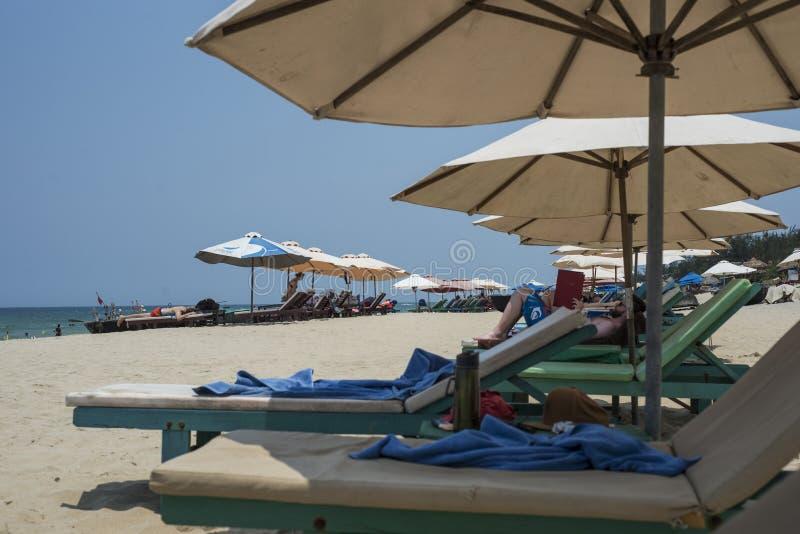 De toeristen ontspannen op lange stoelen onder grote paraplu's op het strand stock foto