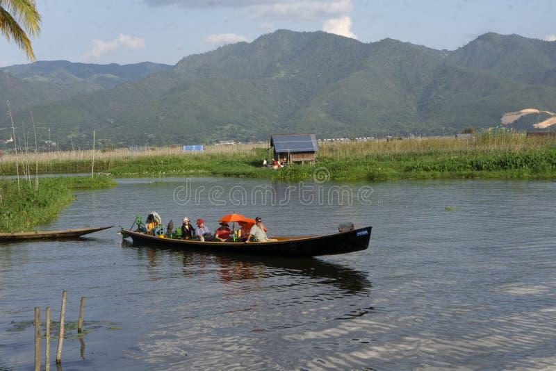 De toeristen op de boot op Inle-Meer in de afstand zijn bergen stock afbeelding
