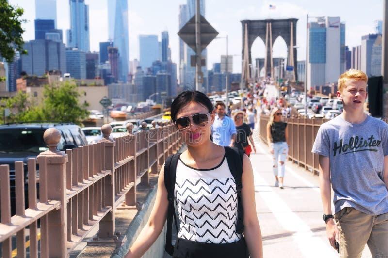 De toeristen op Brooklyn overbruggen en de Stadshorizon van New York daytim stock foto