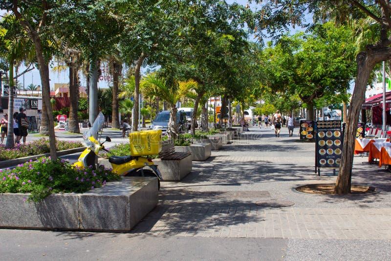 De toeristen op een boom voerden weg met winkels en koffie in Playa DE Las Amerika in het Eiland Tenerife stock fotografie