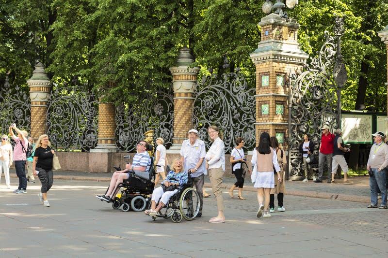 De toeristen in rolstoelen bij de omheining van Mikhailovsky tuinieren bekijken de Kerk van de Verlosser op Bloed Heilige Petersb royalty-vrije stock afbeelding
