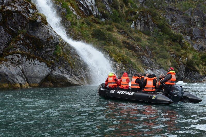 De toeristen van de cruise verschepen dichtbij de watervallen van de gletsjer Nena stock foto's