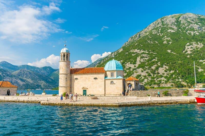De toeristen voeren op een jacht aan het Eiland Gospa od Skrpela in de Boka-Baai van Kotor stock fotografie