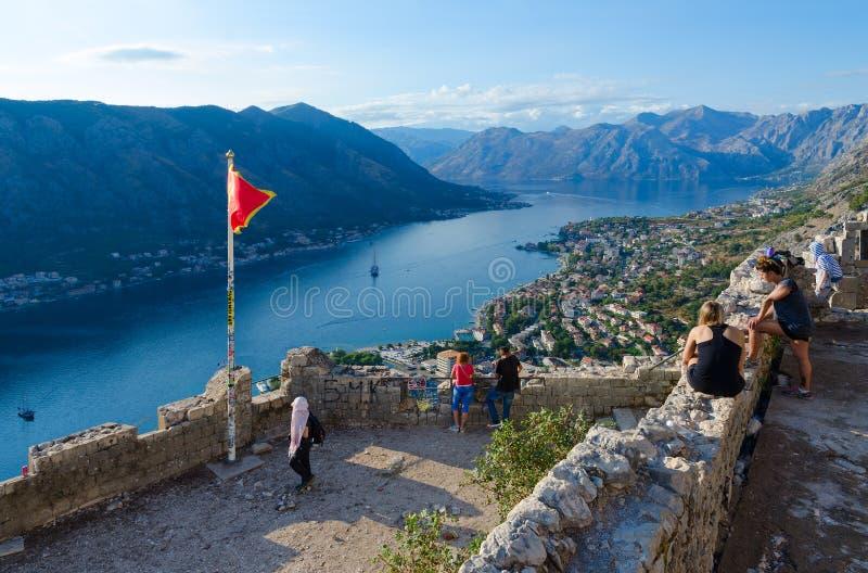 De toeristen zijn op ruïnes van vesting van St John Illyrian Fort over Baai van Kotor, Montenegro stock foto's