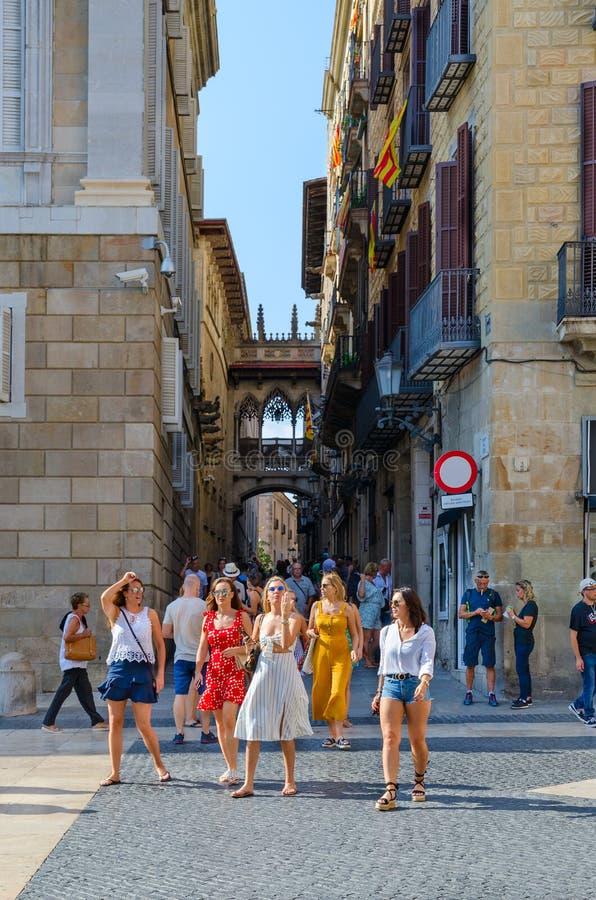 De toeristen zijn op St Jacob Vierkant, Barcelona, Spanje Weergeven van Brug van Sighs Pont dels Sospirs in Gotisch Kwart royalty-vrije stock afbeelding