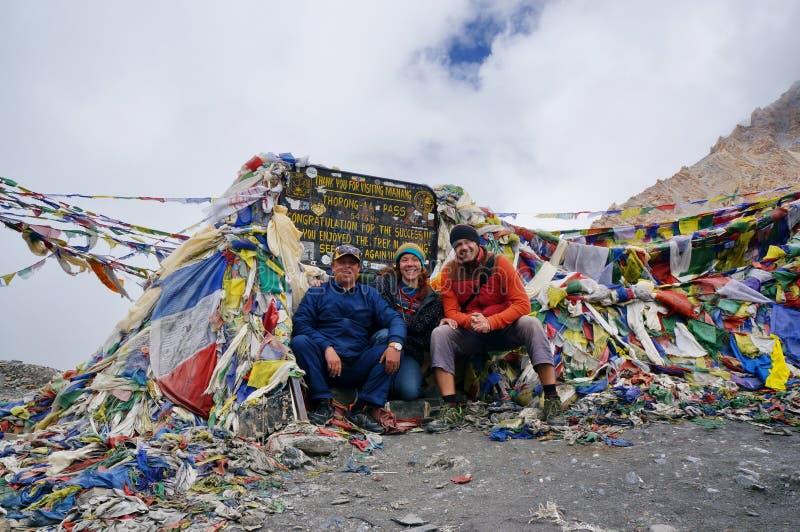 De toeristen zitten op de thorong-La Pas 5416m, de hoogste pas in de wereld himalayagebergte nepal stock afbeelding