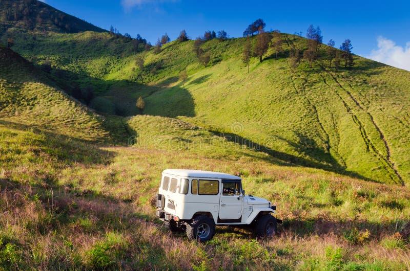 De toeristenauto bij dichtbijgelegen savanneweide zet Bromo-vulkaan op stock fotografie