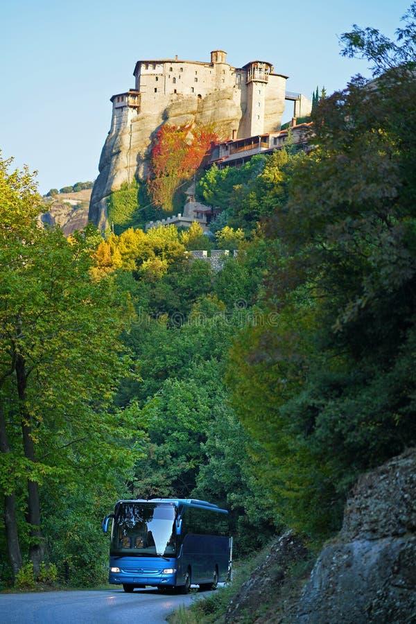 De toeristenbus neemt toeristen om het mooie landschap van Meteora, Griekenland met zijn kloosters, zijn bergen en zijn aard te b stock afbeelding