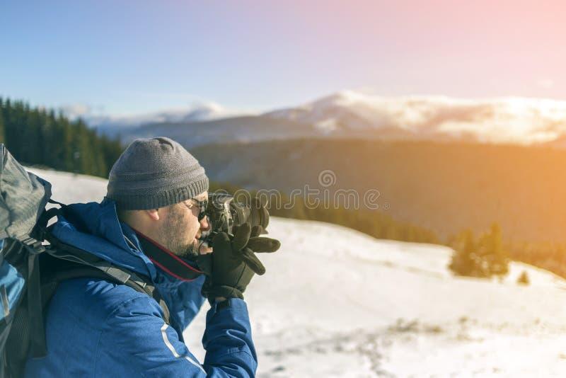 De toeristenfotograaf van de wandelaarmens in warme kleding met rugzak en camera die beeld van sneeuwvallei en bosrijke bergpieke stock afbeeldingen