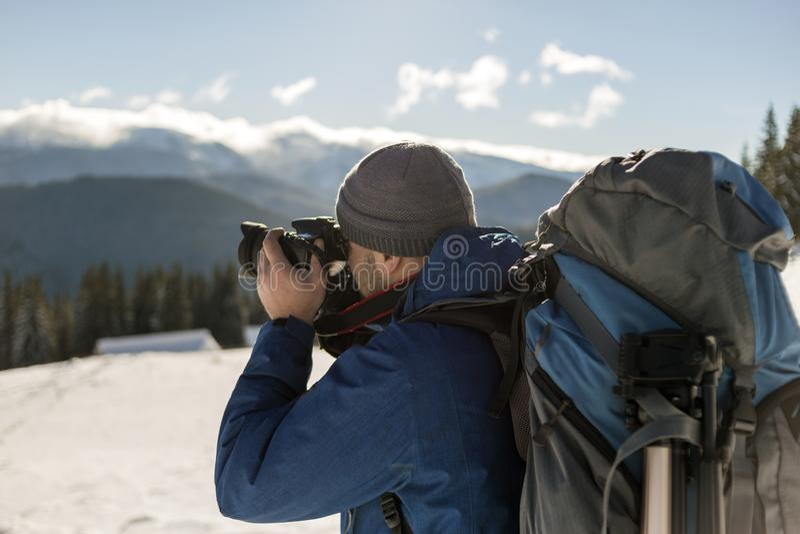 De toeristenfotograaf van de wandelaarmens in warme kleding met rugzak en camera die beeld van sneeuwvallei en bosrijke bergpieke stock afbeelding