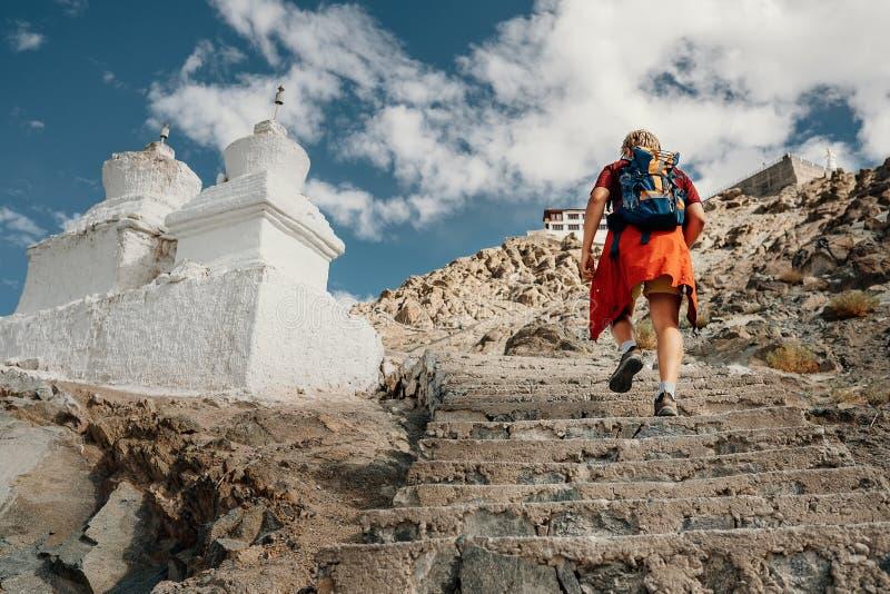 De toeristenmens beklimt op treden aan tibetan heilige plaats in Himalayagebergte m royalty-vrije stock foto