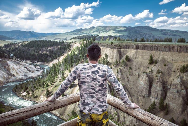 De toeristenmens geniet van de de canionmening van de bergrivier tijdens zijn reisvakantie aan het Nationale Park van Yellowstone royalty-vrije stock foto