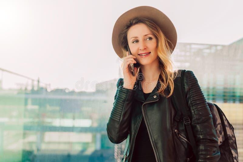 De toeristenvrouw in hoed met rugzak bevindt zich bij luchthaven en spreekt op celtelefoon Meisjestribunes, gebruiks digitaal gad royalty-vrije stock afbeeldingen