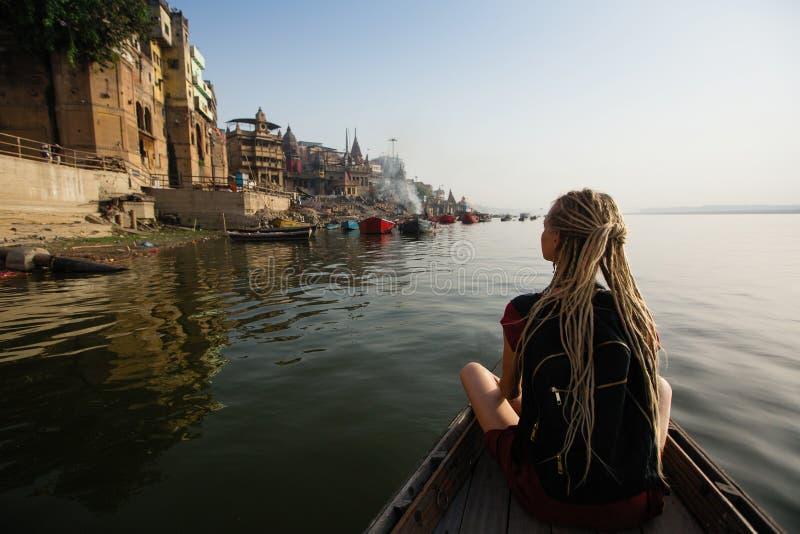 De toeristenvrouw op een boot glijdt door het water op de rivier van Ganges, Varanasi royalty-vrije stock foto's