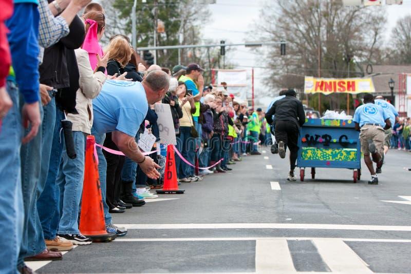 De toeschouwers juichen Team Pushing Bed Toward Finish van Fundraiser-Ras toe stock afbeelding