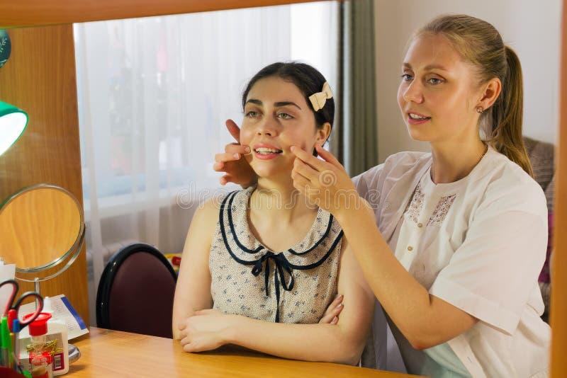 De toespraaktherapeut onderwijst een jong meisje de correcte uitspraak van toespraak royalty-vrije stock fotografie