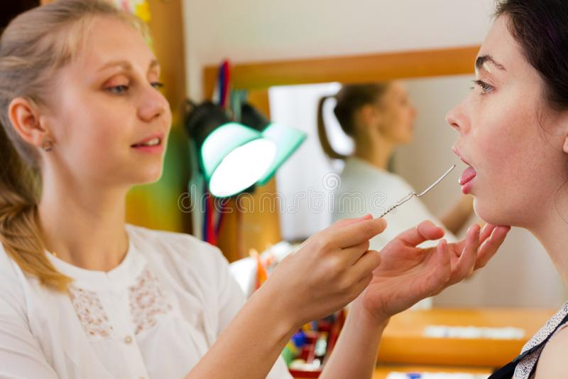 De toespraaktherapeut werkt met de patiënt over de toespraak, die de logopedic sonde de positie van de tong tonen stock foto's