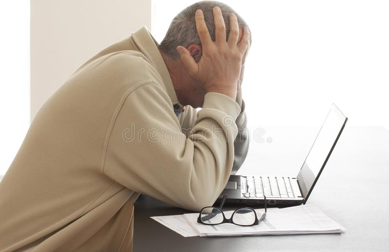 De toevallige geklede mens buigt zijn hoofd over computer in wanhoop terwijl hij zijn hoofd in zijn handen verbergt Paar die glaz stock foto