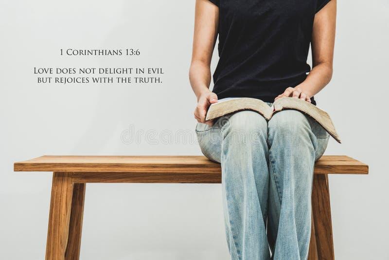 De toevallige jonge vrouw houdt een open Bijbel 1 Corinthians 13:6 op haar royalty-vrije stock fotografie