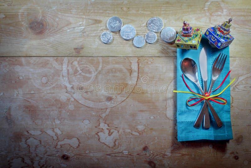De toevallige plaats die van het Chanoekadiner met kleurrijk servet, dreidels, en gelt op oude houten lijst plaatsen royalty-vrije stock afbeelding