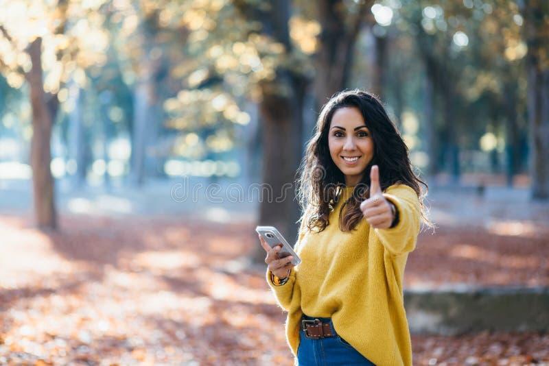 De toevallige vrouw gebruikend smartphone en doend beduimelt omhoog gebaar in aut stock afbeeldingen