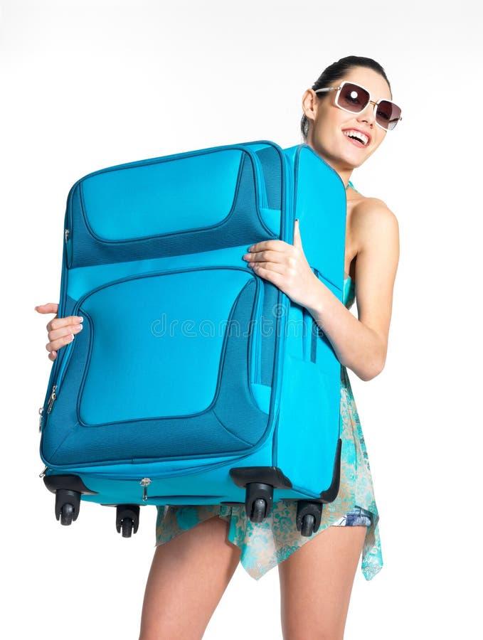 De toevallige vrouw houdt de zware reiskoffer royalty-vrije stock afbeelding