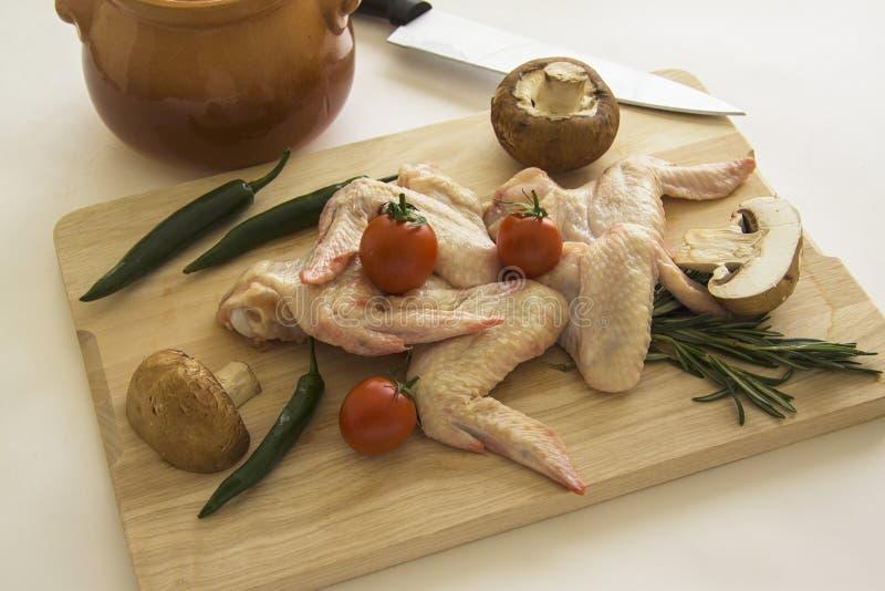 De tomaat, de Spaanse peper en de aardappel van kippenvleugels op scherpe raad royalty-vrije stock foto's