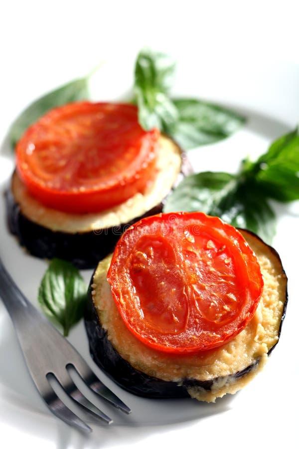 De tomaat en de aubergine bakken stock afbeeldingen