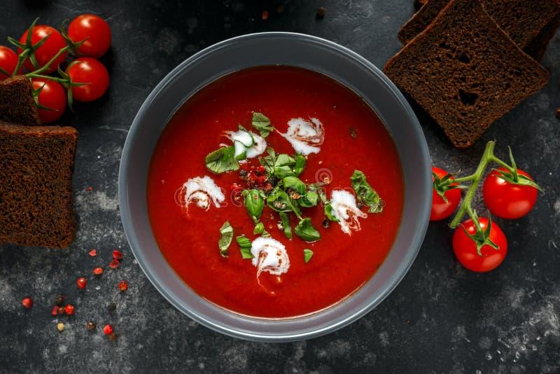 De tomaat en de verse basilicumsoep met knoflook, gebarsten papper korrels, dienden met room en zuurdesembrood stock foto
