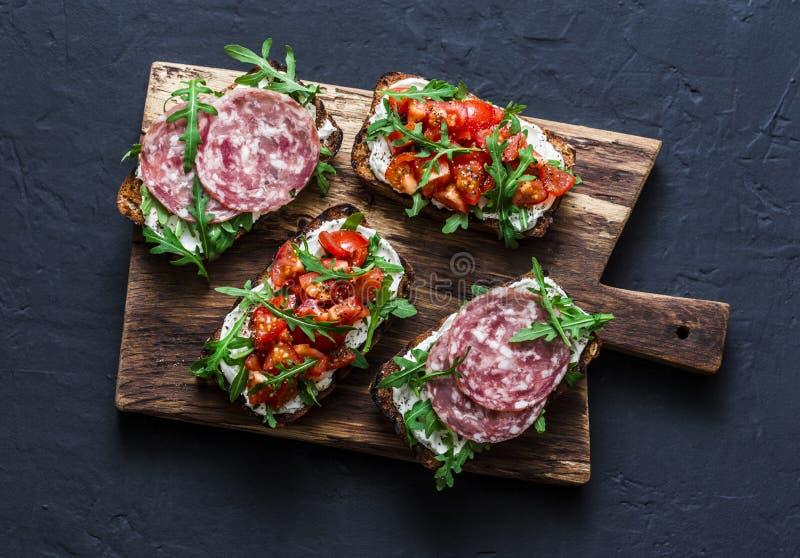 De tomaten, de Italiaanse worst en de gehele korrel van de raketsalade paneren bruschetta op een houten hakbord op een donkere ac stock afbeelding