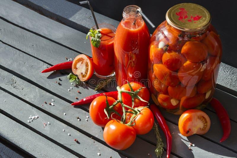 de tomaten, tomatesap in een glas, tomatesap in een fles, blikten tomaten in een kruik in, verse tomaten, peper, munt, rozemarijn royalty-vrije stock afbeeldingen