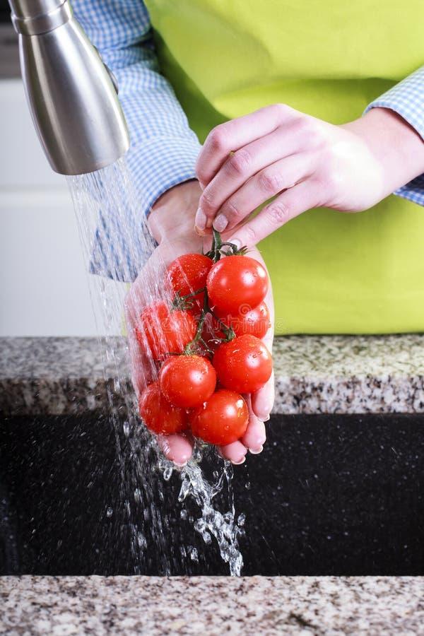 De tomaten van de huisvrouwenwas in water stock foto