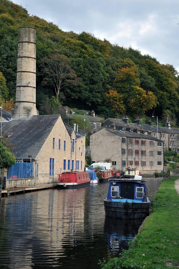 De toneelmening van hebden brug met historische gebouwen langs het kanaal en vastgelegde woonboten met jaagpad en omringend bos stock afbeeldingen