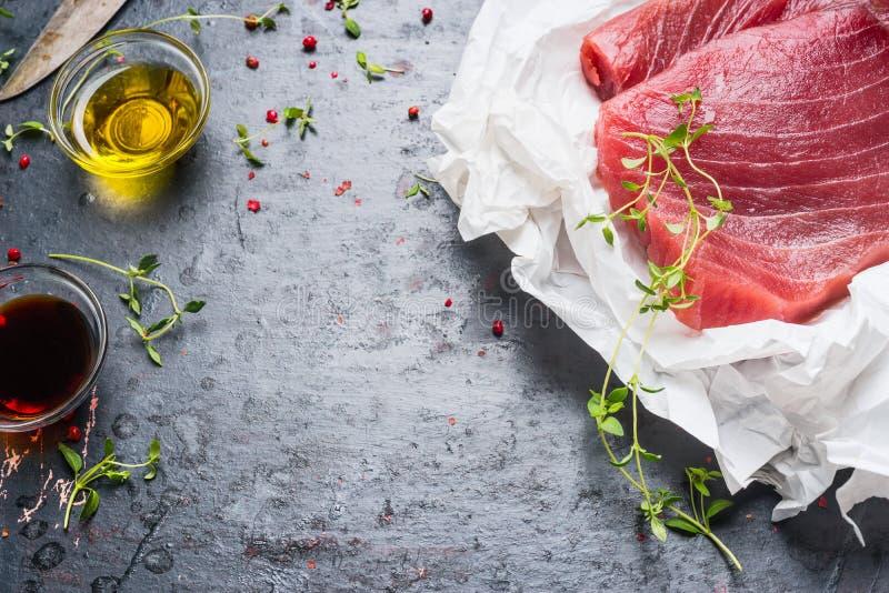 De tonijnlapjes vlees in verpakkend document met het koken van ingrediënten op donkere rustieke achtergrond, sluiten omhoog royalty-vrije stock afbeeldingen