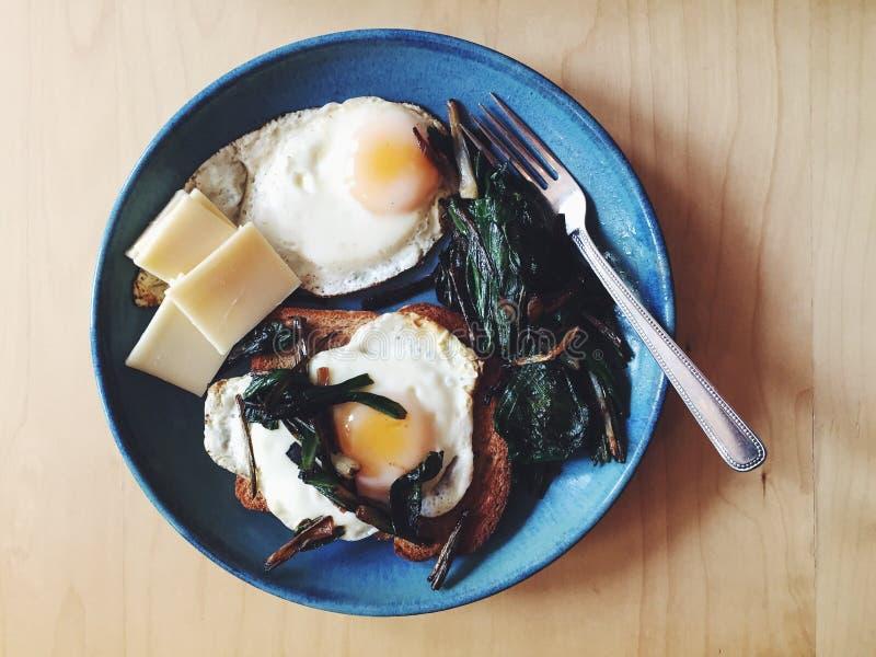 De toost, gebraden eieren met kaas en sauteed hellingen (wilde preien) stock foto's