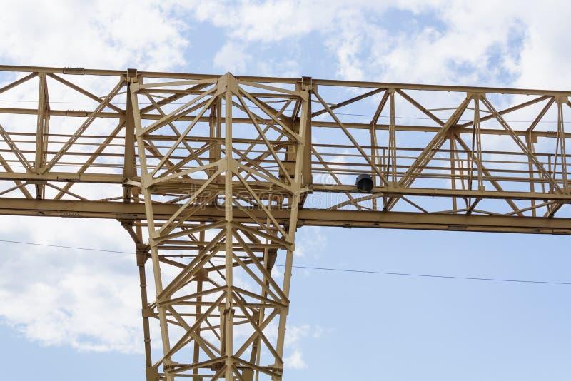 De toren van de bouwkraan op blauwe hemelachtergrond Kraan en de bouw het werk vooruitgang Gele opheffende tapkraan stock afbeeldingen