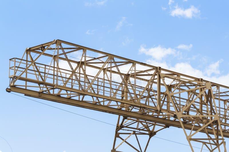De toren van de bouwkraan op blauwe hemelachtergrond Kraan en de bouw het werk vooruitgang Gele opheffende tapkraan stock fotografie