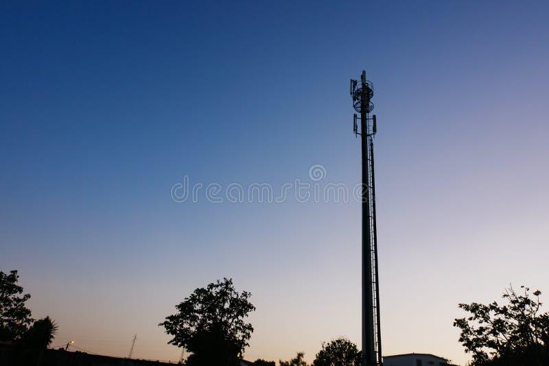 De toren van de celtelefoon/communicatie antenne of mast in silhouet bij schemer stock afbeelding