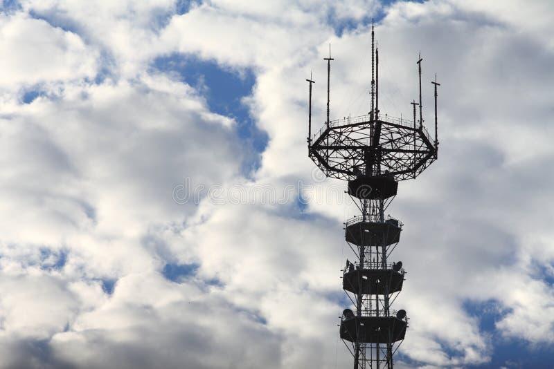 De toren van de telecommunicatie De toren van de kringstelevisie op een achtergrond van witte wolken stock afbeelding