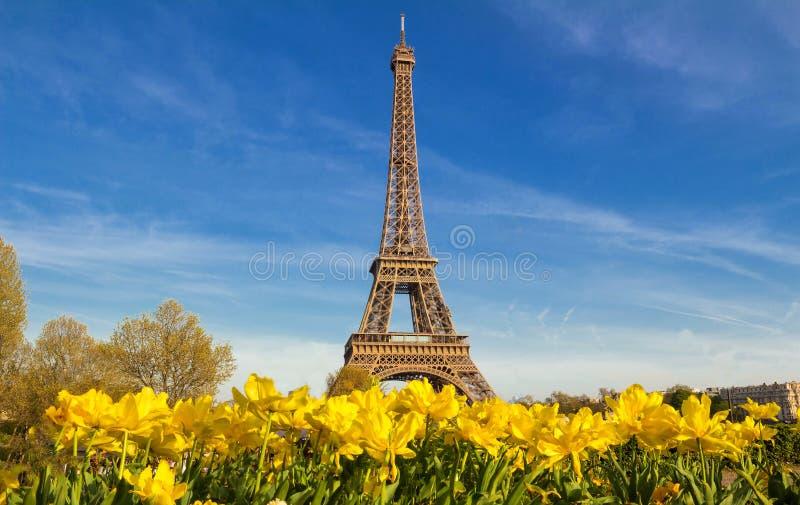 De toren van Eiffel met een trillende blauwe de lentehemel met gele bloemen in voorgrond, Parijs, Frankrijk stock foto