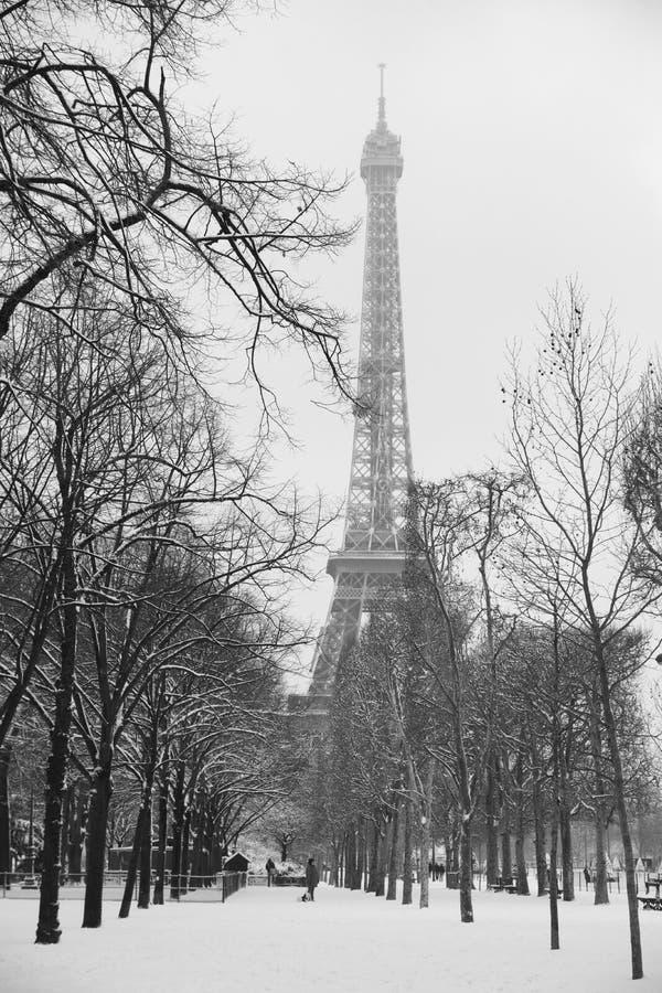 De toren van Eiffel onder de sneeuw en de bomen stock foto's