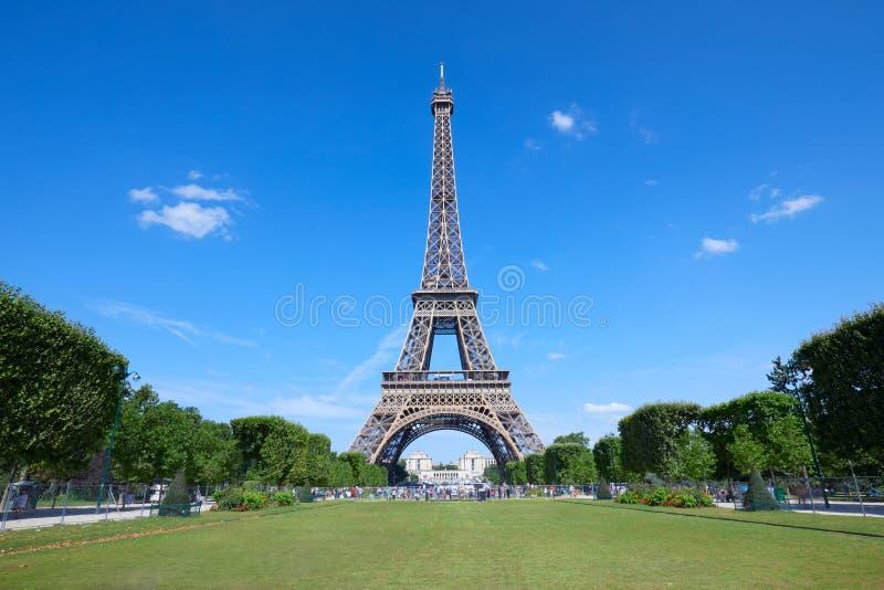 De Toren van Eiffel op Parijs en leeg groen gebied van de weide van Mars in een zonnige dag, duidelijke blauwe hemel stock afbeelding