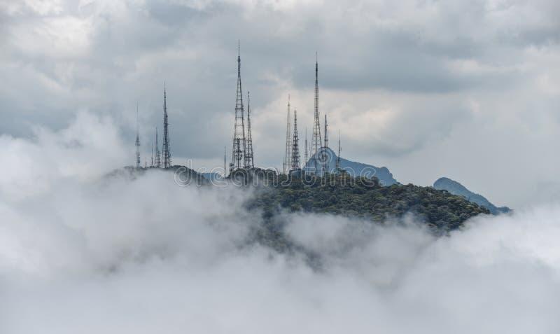 De toren van de machtstransmissie in de mist bij de bergen stock foto