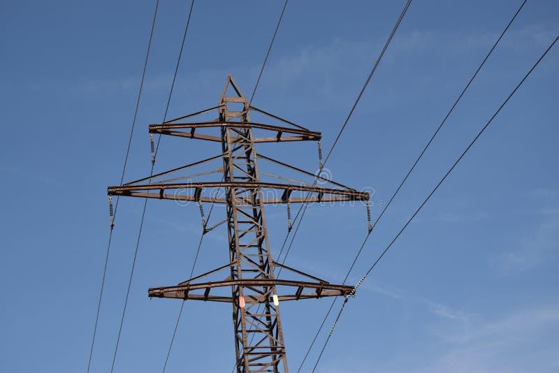 De toren van de machtstransmissie op achtergrond van blauwe hemel stock afbeeldingen