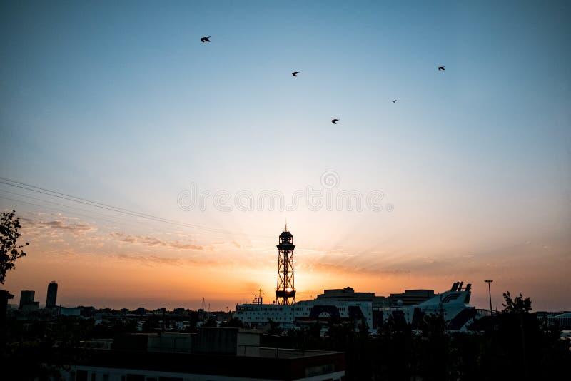 De toren van de Montjuickabelbaan bij dageraad die met zon achter toren tijdens zonsopgang met spectaculaire stralen toenemen, ee stock afbeelding