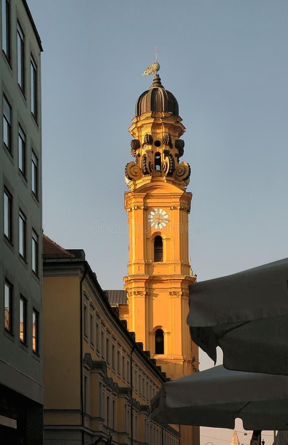 De torenspits van de kerk bij zonsondergang in München, Duitsland stock afbeeldingen