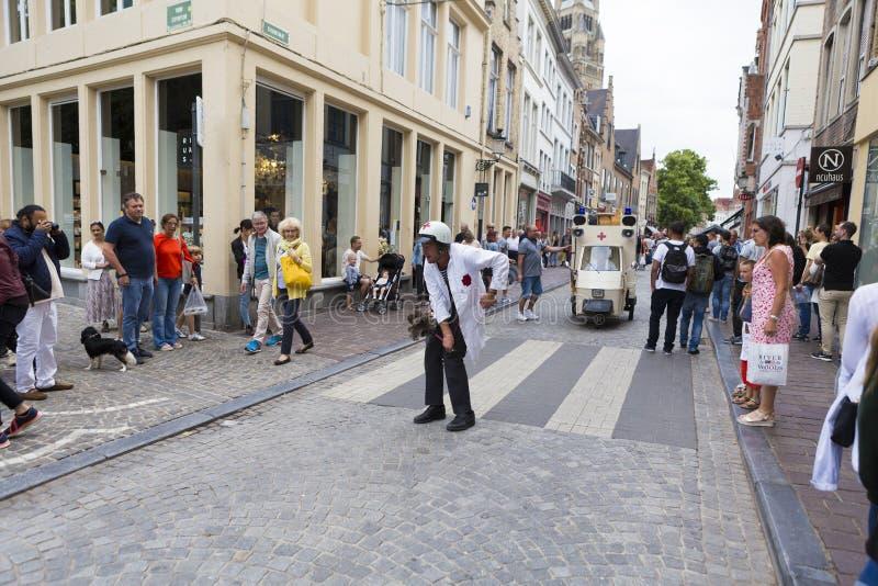 De touristes admirant le m?decin et son ambulance au carnaval de Bruges image libre de droits