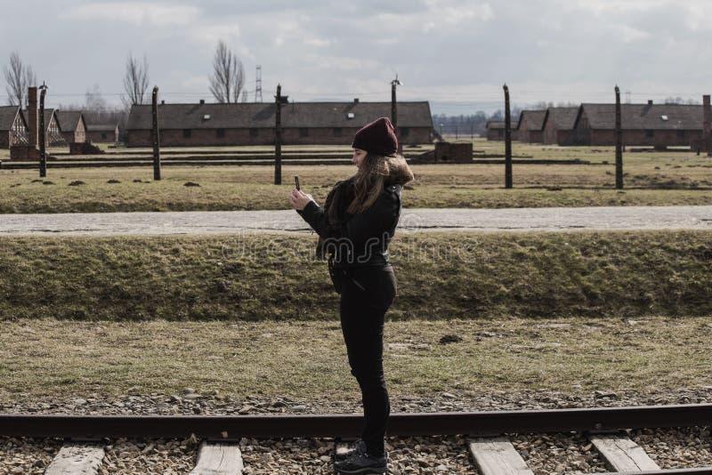 De touristes faisant une photo sur le chemin de fer menant à l'entrée principale du camp de concentration d'Auschwitz Birkenau, P images libres de droits