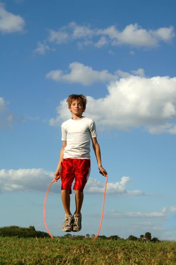 De touwtjespringen van de jongen stock foto's
